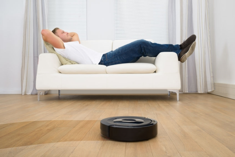 Man Relaxing While Roomba Working Hard