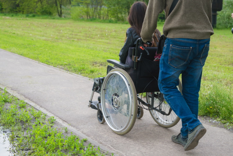 A man carries a woman in a wheelchair on the way