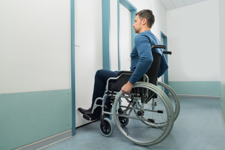 Man in Wheelchair Looking to Open Door