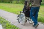 Pushing Wheelchair on Pathway